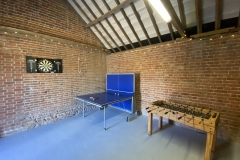 The garage games room has a table tennis table, dart board and table football table